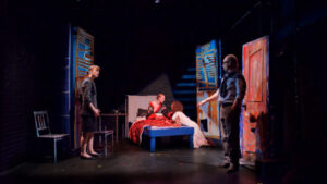 Actors are shown on a stage. Blue and Red hues contrast the dark tones.
