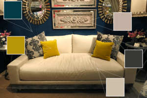 Showroom for Peninsula Home Collection Company has a deep blue wall, metallic wall hangings, a cream couch, and bright yellow throw pillows