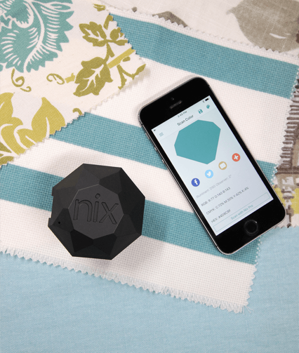 The Nix Pro sits on top of several fabric samples. A phone beside it displays the colour the Nix was scanning.