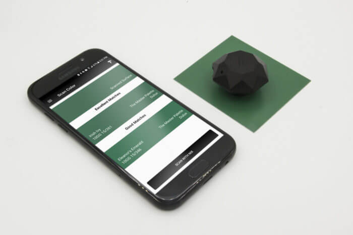 The Nix Mini is scanning a green metal swatch, the results are displayed on a phone