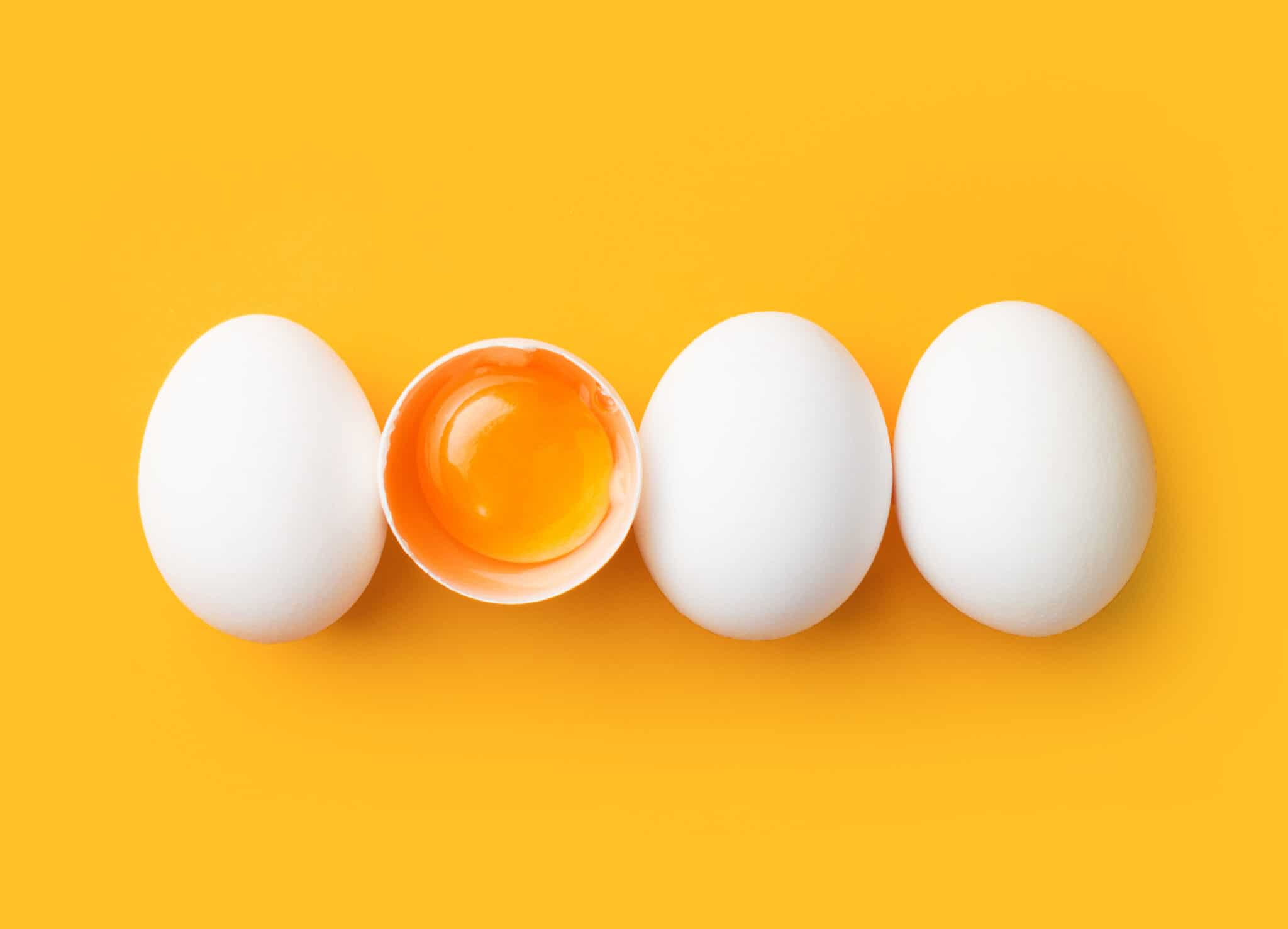 Egg yolk in egg shell with 3 other eggs