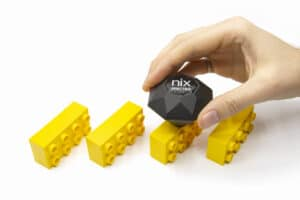 A hand holds the Nix Spectro and scans a yellow building block.